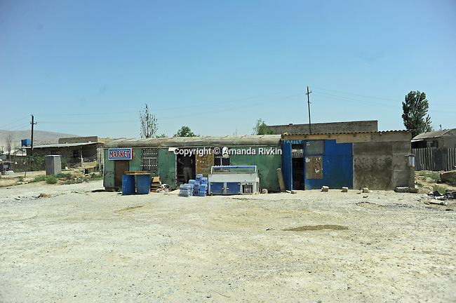 A market at the foot of the Khazar Islands serves an illegal refugee settlement that is to be moved to make way for the Khazar Islands project in Sahil, Azerbaijan on July 18, 2012.  The brainchild of Ibrahim Ibrahimov, the artificial Khazar Islands project just southwest of the Azerbaijani capital Baku is being built at a projected cost of $100 billion with an anticipated 800,000 housing units; evictions in Azerbaijan are often forceful with police storming a house and leaving those evicted with no legal recourse, options or reimbursement.
