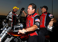Nov 10, 2013; Pomona, CA, USA; Matt Hines (center) congratulates NHRA pro stock motorcycle rider Eddie Krawiec and crew after winning the Auto Club Finals at Auto Club Raceway at Pomona. Mandatory Credit: Mark J. Rebilas-
