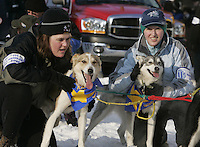 Rookie musher Eric Roger's handlers hold his dogs at  the Anchorage start line on 4th avenue during the start of the Iditarod.