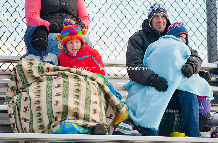 WATERTOWN, CT 112813JS08-Football fans, from left, Duncan Longley, 10, of Lakeville with family friends Susanna Langan, 11, David Langan and Phoebe Langan, 6, all of Morris, bundle up from the cold temperatures as they watch the annual Thanksgiving Day game between Torrington and Watertown Thursday at Watertown High School. <br />  Jim Shannon Republican-American