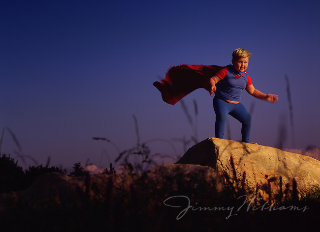 A young chubby boy dressed up as superman poses on a rock in a field pretending to be a superhero.