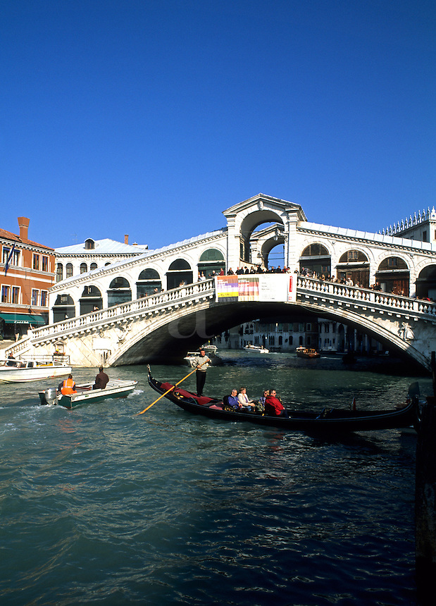 Gondola ride in canal approaching the famous Rialto Bridge in picturesque Venice Ital