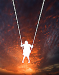 Silhouette of a child on a swing against the setting sun.