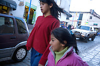 TWO YOUNG GIRLS WALKING HAND IN HAND ON THE SREETS OF CUZCO PERU