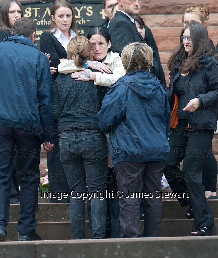 A unknown family member, still handcuffed to a G4S officer, is greeted by Kim Haney (cream coat) at the funeral of former crime family matriarch Mags Haney at St Mary's RC Church in Stirling.