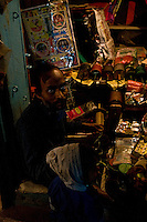 During the day hundreds of kites can be seen flying over Varanasi.  At night the kite seller minds his stall in the semi darkness fixing and making kites ready for sale. (Photo by Matt Considine - Images of Asia Collection)