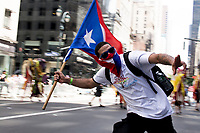 A participate of the Puerto Rican Day Parade runs down Fifth Avenue & 43 Street waving the flag of Puerto Rico behind him.