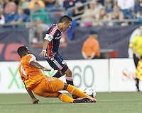Houston Dynamo defender Jermaine Taylor (4) thwarts New England Revolution midfielder Diego Fagundez (14) attack. In a Major League Soccer (MLS) match, Houston Dynamo (orange) defeated the New England Revolution (blue), 2-1, at Gillette Stadium on July 13, 2013.