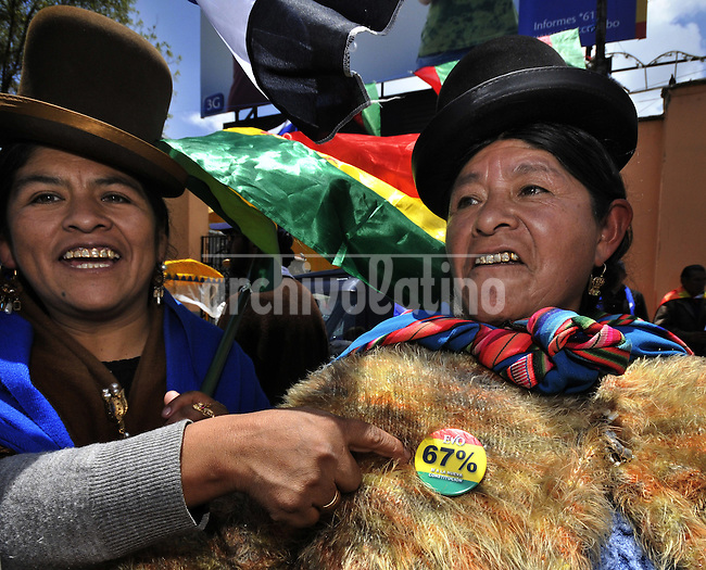 Two Aymara indians with their typical huts show a button in support of the new political constitution that President Evo Morales will try to pass in Bolivia next January 25th, 2009.