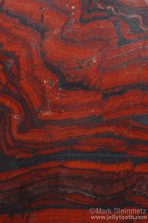 Banded Iron Formation, Upper Peninsula, Michigan, USA. Precambrian, ~ 2.5 billion years old.  Banded Iron Formations, also called BIFs, represent a time when Earth's atmosphere contained significant amounts of oxygen produced for the first time from marine organisms as a byproduct of photosynthesis. Bands consist of repeated layers of silver to black iron oxides (such as hematite or magnetite), alternating with bands of iron-poor shales and silica (cherts or jasper) often red in color.