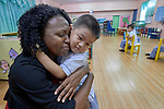 Donna Akuamoah, an international program officer for United Methodist Women, hugs a child in school at Harris Memorial College in Manila, Philippines, on January 16, 2018. Akuamoah was in the Philippines with other UMW staff to meet with women from throughout the region, and visit UMW-supported mission institutions.