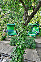Two green chairs are set on a decked terrace area in a garden against the backdrop of an ivy covered wall. Ivy grows its way up the trunk of a nearby tree, which provides shade on a sunny day.