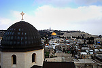 A general view from the tower of the Church of Redeemer shows the Dome of the Rock mosque, Islam's third holiest site, and the cross of the Church of the Holy Sepulchre in the old city of Jerusalem, on February 17, 2014 .Israeli television Channel 7 said on Sunday that the Israeli Occupation municipality in Jerusalem approved on Friday the construction of 350 housing units in the settlement of Talpiot in east Jerusalem. Photo by Saeed Qaq