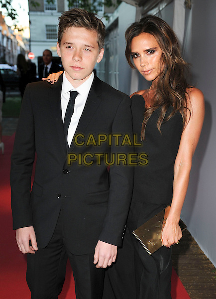 Brooklyn and Victoria Beckham<br /> Glamour Women of the Year Awards - Outside arrivals - at Berkeley Square Gardens, London, England.<br /> June 4th 2013<br /> half length black suit suit white strapless jumpsuit clutch bag hand arm over shoulder gold mother mom mum son<br /> CAP/PP/GM<br /> &copy;Gary Mitchell/PP/Capital Pictures