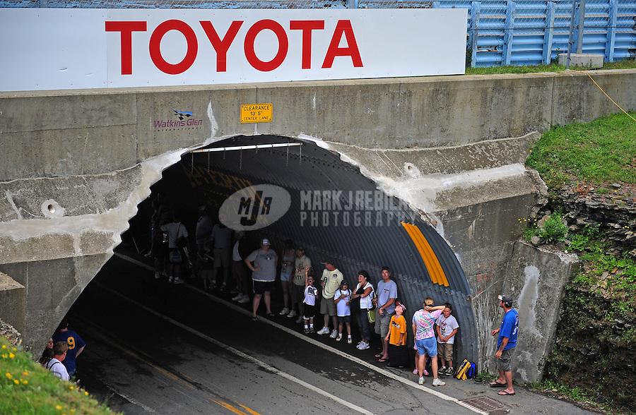 Aug. 9, 2009; Watkins Glen, NY, USA; NASCAR Sprint Cup Series take shelter under a tunnel as it rains during a delay in the Heluva Good at the Glen at Watkins Glen International. Mandatory Credit: Mark J. Rebilas-