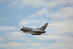 Hawker 800XP corprorate turbo jet taking off into blue sky and clouds from Buchanan Field airport, California
