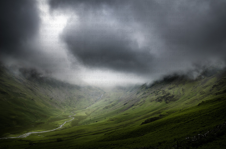 Dark clouds over a green valley