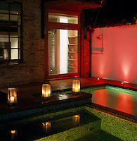 At night this outdoor swimming pool is lit with a combination of candlelight and red spotlights