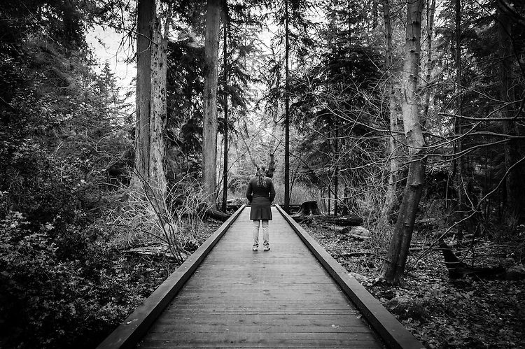 A woman standing along a wooden trail leading into a forest.