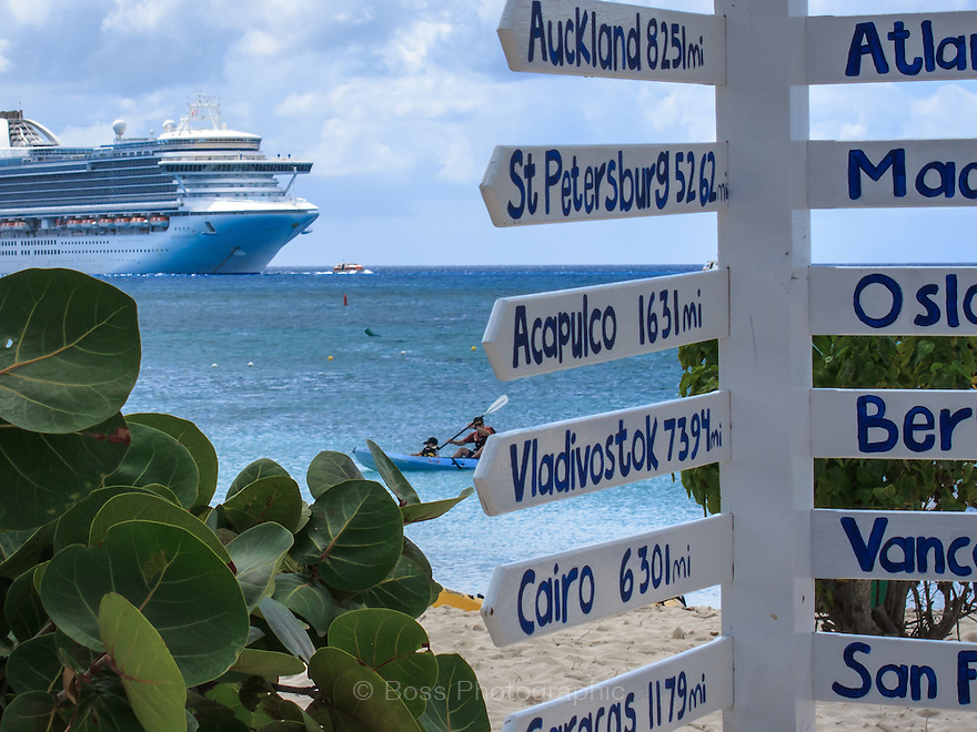 SIgn on a beach showing distance to cities around the world with cruise ship in the background, Princess Cays, Eleuthera, Bahamas