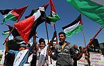 """Palestinians hold placards and the national flags during a rally against """"Deal of the Century"""" and to announce the launch of the great return march near the border with Israel in east of Gaza city on March 17, 2018. Photo by Ashraf Amra"""