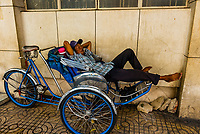 Man taking a nap on a cyclo (a three-wheel bicycle taxi), Ho Chi Minh City (Saigon), Vietnam.