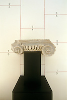 The capital from an ancient column is displayed on a plinth against some minimalist built-in cupboards in the kitchen-diner of a house designed by Oswald Mathias Ungers