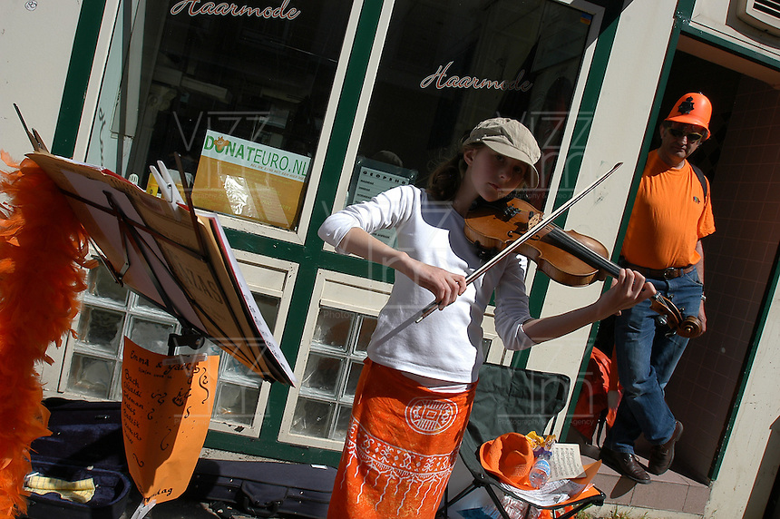 AMSTERDAM-HOLANDA- Una jovencita toca el violín en una calle durante el día de la Reina./ A young woman palying the violin int he street during the Queen's day.   Photo: VizzorImage/STR