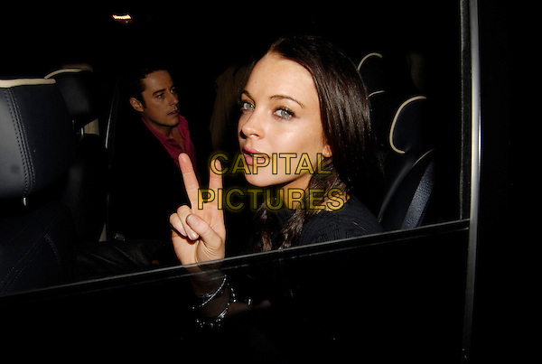 LINDSAY LOHAN.Leaving Volstead Club, London, England, .in the early hours of November 19th 2006..portrait headshot in car window hand fingers peace sign gesture.CAP/SW.©Stephen Walters/Capital Pictures.