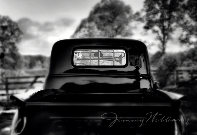 A trombone sits on a gun rack in the back window of an old black pick up truck
