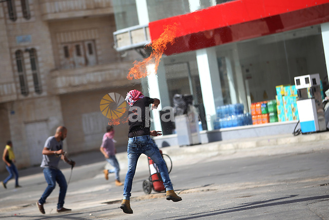 A Palestinian protester throws a molotov cocktail at Israeli security forces during clashes near the Jewish settlement of Bet El, near the West Bank city of Ramallah, on October 13, 2015. A wave of stabbings that hit Israel, Jerusalem and the West Bank this month along with violent protests in annexed east Jerusalem and the occupied West Bank, has led to warnings that a full-scale Palestinian uprising, or third intifada, could erupt. The unrest has also spread to the Gaza Strip, with clashes along the border in recent days leaving nine Palestinians dead from Israeli fire. Photo by Shadi Hatem