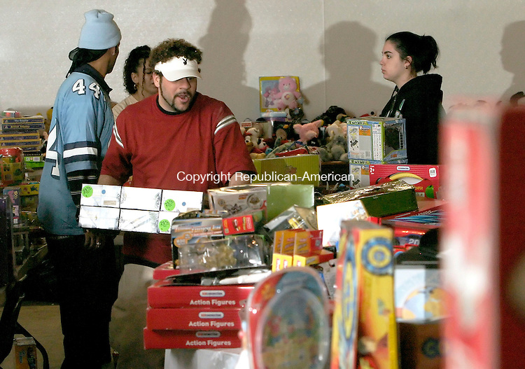 WATERBURY, CT -14 DECEMBER 2005 -121405J04---Peter Morales of Waterbury, center, was among the volunteers to help set up the Greater Waterbury Interfaith Ministries annual toy shopping day to be held Thursday at St. Johns Episcopal Church in Waterbury. More than 300 children will  receive gifts and their families will receive food for the holidays. According to Sue Pronovost, director of administration and resources, the program would not be possible without the donations from Connecticut State Troop A of Southbury, Toys for Tots, Campion Ambulance and member churches.    --  Jim Shannon Republican-American--Peter Morales; Waterbury; Greater Waterbury Interfaith Ministries; Sue Pronovost are CQ