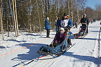 Abbie West and team run past spectators on the bike/ski trail during the Anchorage ceremonial start during the 2014 Iditarod race.<br /> Photo by Britt Coon/IditarodPhotos.com
