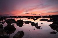Orange sunset reflecting off of tide pool at Shark's Cove, Oahu