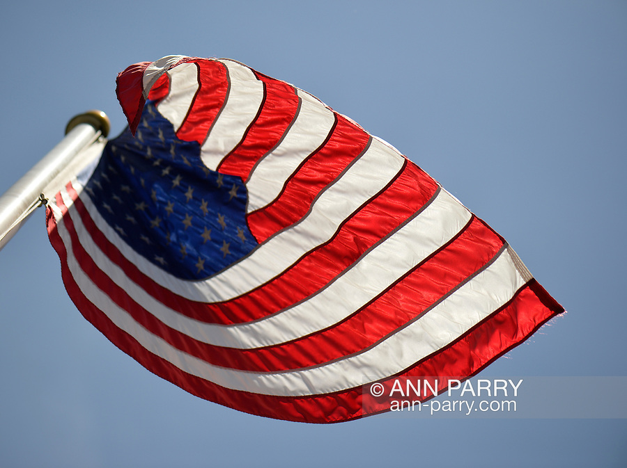 Merrick, New York, U.S. - May 26, 2014 - The American flag flies, waving in the wind, during the Merrick Memorial Day Parade and Ceremony, hosted by American Legion Post 1282 of Merrick, honoring those who died in war while serving in the United States military.