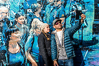 """New York, NY - 23 October 2016 Couple taking a selfie in front of Logan Hicks mural """"the Story of my life."""" Bowery Mural ©Stacy Walsh Rosenstock"""