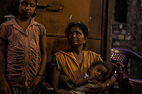 "Sonamoni Hembrom, 32 year old, photographed with her 2 children, lives in the slum of Balaram, in Jamshedpur. In 1995, her mother was accused of witchcraft and her father killed by some fellow villagers, who feared he might report to the police the accusations against the wife. The family had to leave the village of Chimihatu and all its properties behind. Two of her brothers were able to go back to their house only one month ago. ""Every night I feel so anxious that something might happen to them"", she says."