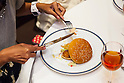 A customer enjoys eating a ''Fresh Mac'' burger with fork and knife as a part of McDonald's special dinner during a Restaurant M event in the posh Roppongi Hills area on July 27, 2015, Tokyo, Japan. 20 chosen diners (from 8,300 applications) ate a special multi-course dinner created by the celebrity chef using ingredients from the restaurant chain's regular menu. The special one-night only event was organized to celebrate the launch of its new summer menu ''Fresh Mac,'' which features fresh vegetables. The five-course meal served on a white tablecloth with plates and proper cutlery included a Vichyssoise en Pommes de terre de McDonald, Mousse au Poivron Rouge, Salade en Gelee aux Legumes de McDonald, Cinq Pinchos des McDonald Patties avec leur Sauces, a choice of main dish including the Fresh Mac Bacon Lettuce Burger, and a McFlurry Mixed Berry Oreo dessert with a Premium Roast Coffee. (Photo by Rodrigo Reyes Marin/AFLO)
