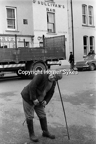 Killorglin Eire Southern Ireland. Workman using a listening stick with ear piece, listening for water vibrations underground. Water dowsing or divining, ie looking for water underground. In this case a burst pipe. 1970s.He is trying to 'hear' the water. 1972.