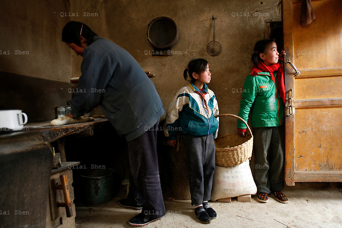 IFADHuinin_147 11-year-old He Juan and 9-year-old He Hong stand in the kitchen while a neighbor helps with the cooking at their home in Linfang Village, Zhaisuo Township, Huinin County, Gansu Province on 20th March 2006.