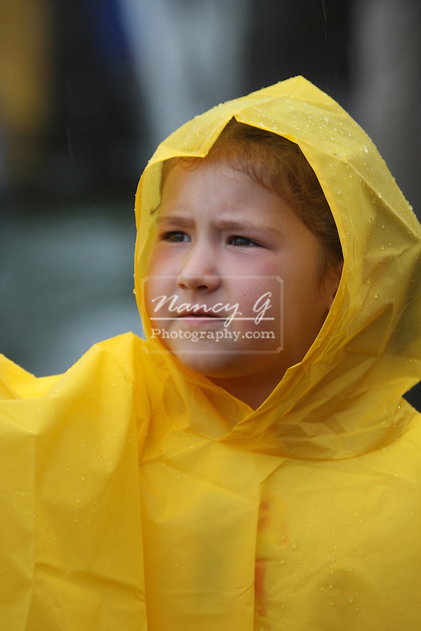 A young child in a yellow rain poncho or jacket