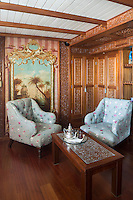 A corner of the master bedroom suite features a series of carved built-in wardrobes and is furnished with a pair of upholstered armchairs