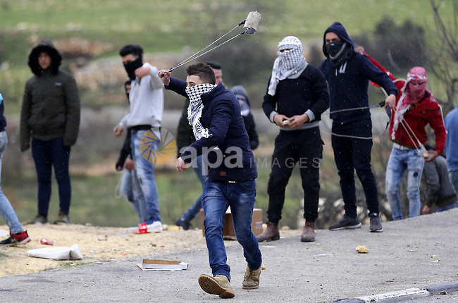 Palestinian protesters clash with Israeli security forces following the funeral of Hamza Zamareh in Halhoul, in the West Bank city of Hebron on February 17, 2018. Hamza stabbed a security guard at the entrance of the Israeli settlement Karmei Tzur north of Hebron and was shot dead, the Israeli army said, in the latest violence in the occupied West Bank. Photo by Wisam Hashlamoun