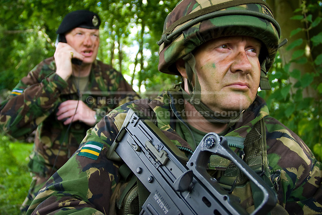 On guard outside a command post, a Territorial Army Squadron sergeant major from the Royal Yeomanry (foreground) and the regimental training officer (a regular major of the Royal Tank Regiment), keep watch for potential enemy attack.