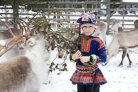 Arctic Finland. Jouna, a Lapland Sami boy feeding the deer at Sami's reindeer farm.