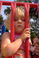 Girl age 2 looking through bars on playground.  St Paul Minnesota USA