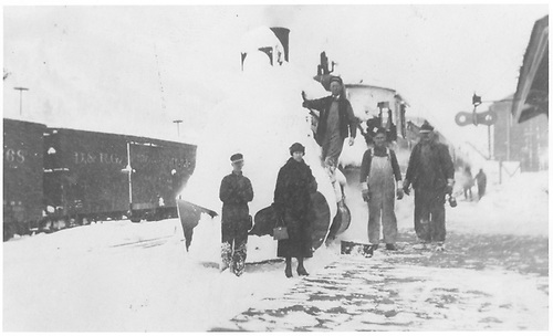 A southbound RGS passenger train has arrived in Rico heavily-clad in snow with two passengers and three crew posed in front of the locomotive.<br /> RGS  Rico, CO