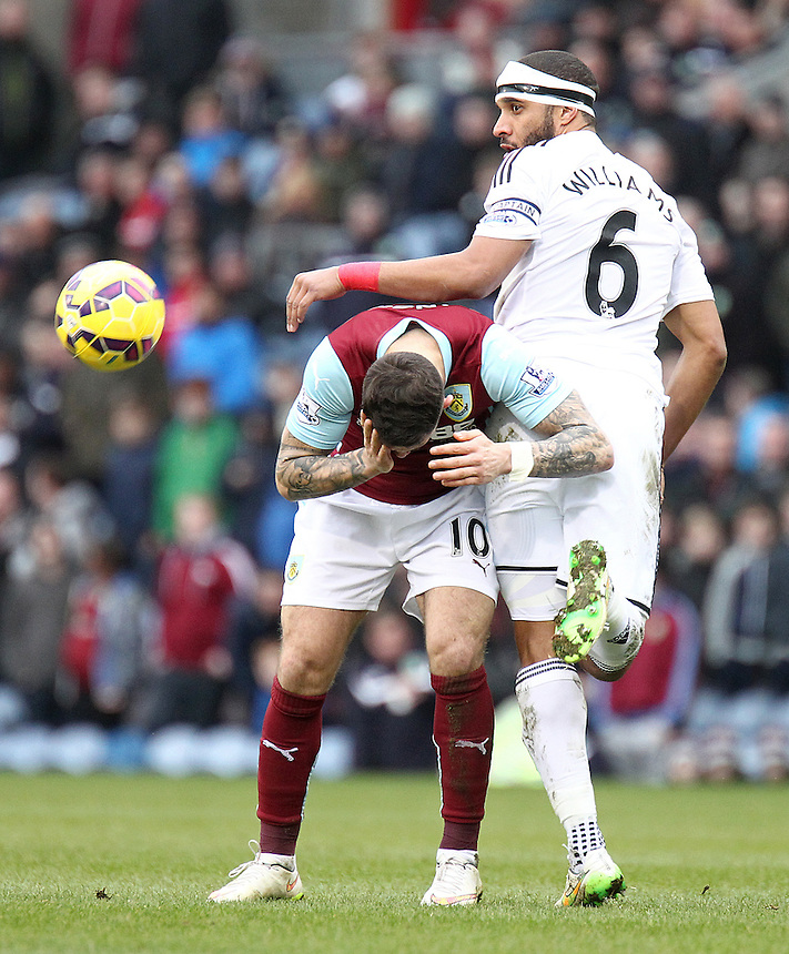 Burnley's Danny Ings reacts to an apparent arm to the head challenge from Swansea City's Ashley Williams<br /> <br /> Photographer Rich Linley/CameraSport<br /> <br /> Football - Barclays Premiership - Burnley v Swansea City - Friday 27th February 2015 - Turf Moor - Burnley<br /> <br /> &copy; CameraSport - 43 Linden Ave. Countesthorpe. Leicester. England. LE8 5PG - Tel: +44 (0) 116 277 4147 - admin@camerasport.com - www.camerasport.com