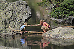 Blond Caucasian women helping her daughter cross a log bridge at Maroon Lake, Elk Mountains, west of Aspen, Colorado.