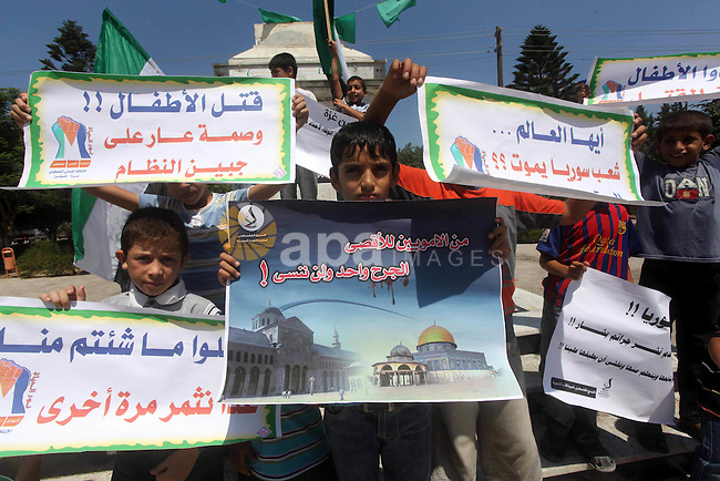 Palestinian children hold a Syrian revolution flag during a protest against Syria's President Bashar al-Assad and support of Syrian Children  at the Al joundi Al Majhoul in Gaza City on July 28, 2012. Photo by Ashraf Amra